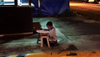 Мальчик делает уроки при свете Макдональдса